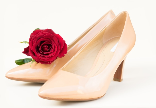 Nude colored high heels still life with fresh red rose bud