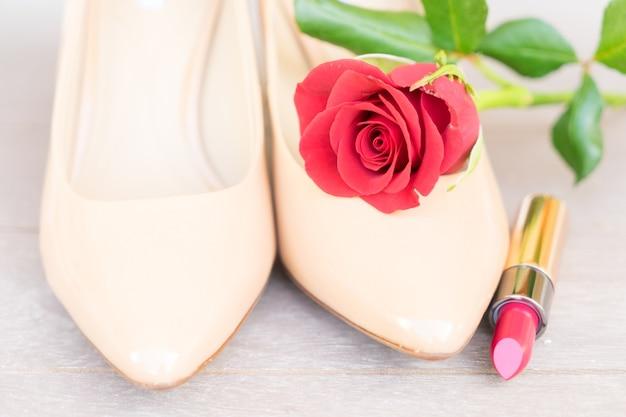 赤いバラと口紅のあるヌードカラーのハイヒールの静物