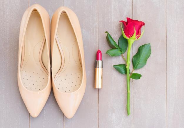 赤いバラのつぼみと口紅、上面図とヌード色のハイヒールの静物