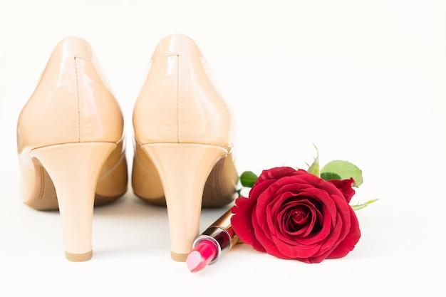 赤いバラのつぼみと口紅のあるヌードカラーのハイヒールの静物