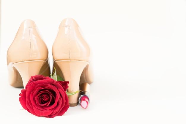 赤いバラのつぼみの花と口紅のあるヌードカラーのハイヒールの静物