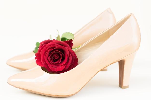 赤いバラのつぼみの花とヌード色のハイヒールの静物
