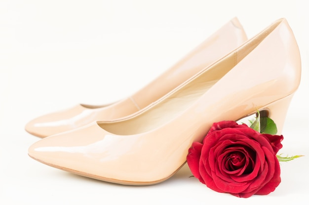 Nude colored high heels still life with red rose bud