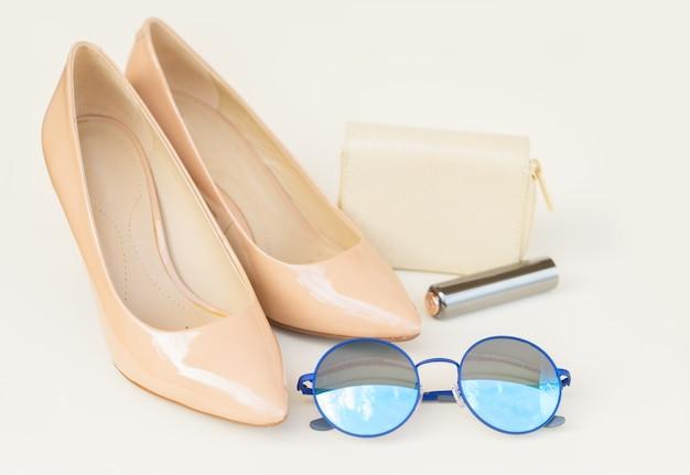 財布、青いサングラス、口紅のあるヌードカラーのハイヒールの静物