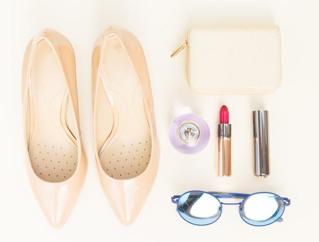 財布、メガネ、赤い口紅のあるヌードカラーのハイヒールの静物