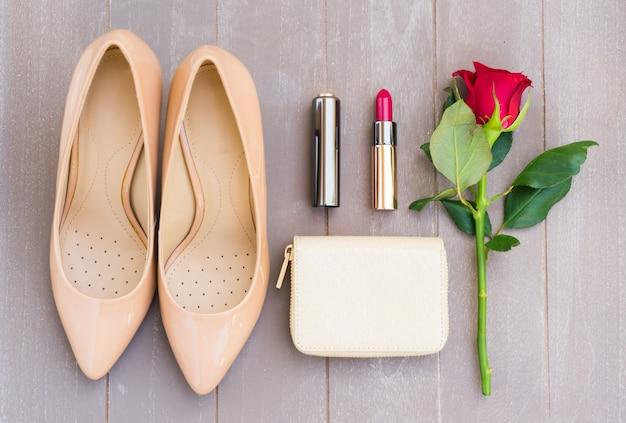 財布、バラの花、赤い口紅のあるヌードカラーのハイヒールの静物