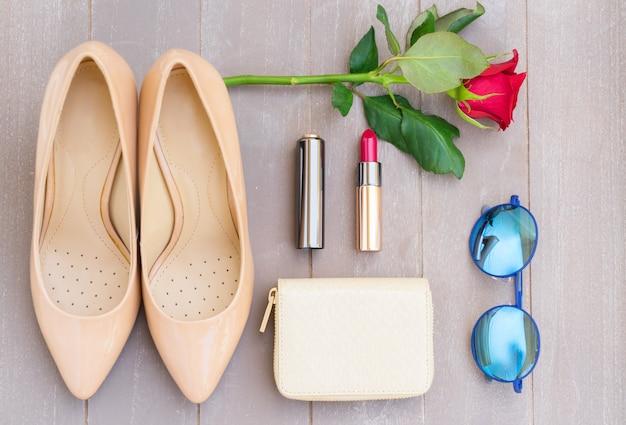 財布、バラの花、サングラス、赤い口紅のあるヌードカラーのハイヒールの静物