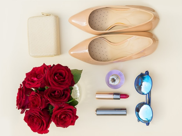 財布、バラ、サングラス、赤い口紅のあるヌードカラーのハイヒールの静物