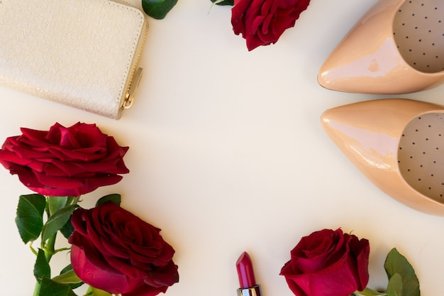 Nude colored high heels with lipstick, fresh red roses and wallet hero header
