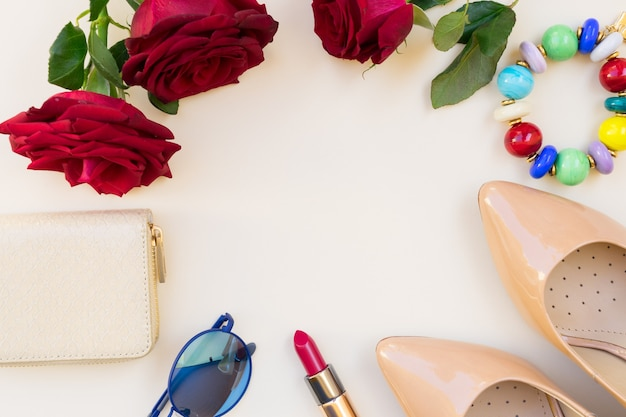 Nude colored high heels with lipstick, glasses, red roses and wallet flat lay scene