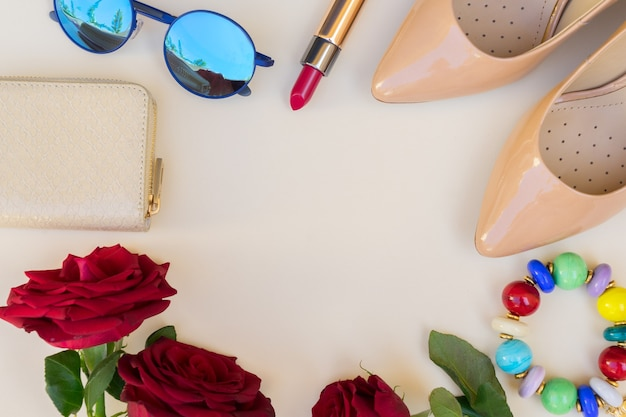Nude colored high heels with lipstick, glasses, red roses and wallet hero header