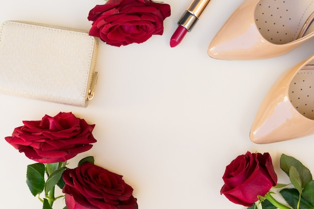 Nude colored high heels with lipstick, red roses and wallet hero header
