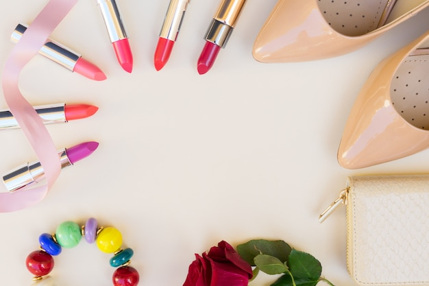 Nude colored high heels with lipsticks and wallet hero header
