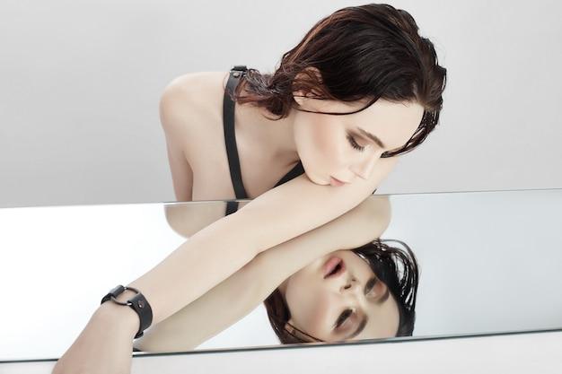 裸のファッションの女性は、鏡に横になり、反射を見ます。濡れた髪の女の子、顔のスキンケア。テキスト、copyspace の場所