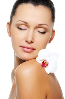 肩に花の蘭が付いている裸の女性の身体