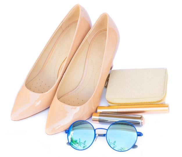 白い背景で隔離の財布、サングラス、口紅と裸のハイヒールの静物