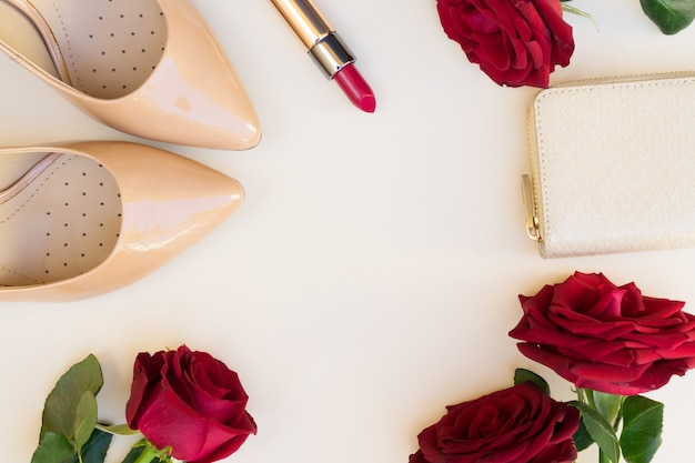 Nude high heels with lipstick, fresh red roses and wallet hero header