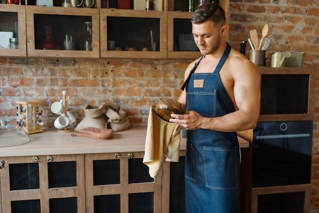 앞치마를 입은 누드 남편이 부엌에서 접시를 닦습니다. 집에서 아침 식사를 준비하는 벌거 벗은 남성 사람, 옷없이 음식 준비