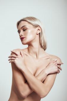 彼女の手で彼女の胸を覆っているブロンドの髪を持つ裸の女性セクシーなスリムな女性