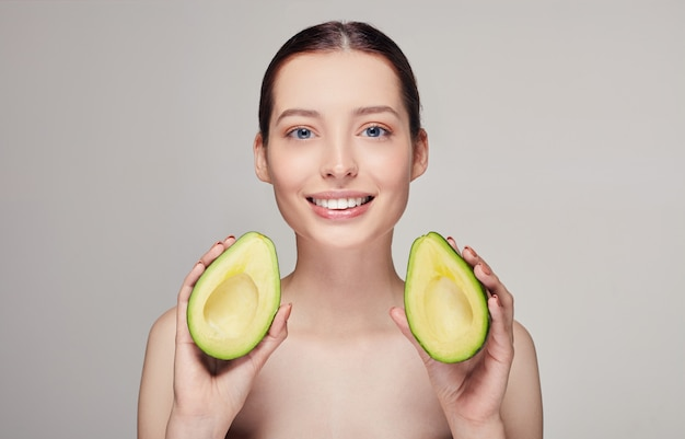 Nude lady with perfect smile and avocado in hands