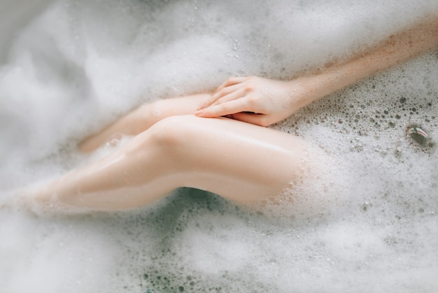 泡でお風呂に横たわっている女性の裸の脚、上面図。バスルームでのリラクゼーション、健康、スキンケア