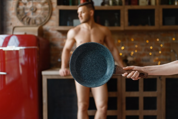 裸の愛のカップルが一緒にキッチンで料理。裸の男と女の家で朝食を準備、服なしの食品の準備