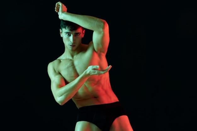 黒の背景に彼の手で身振りで示す裸の男性アスリート