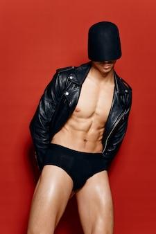Обнаженный спортсмен-мужчина в черных шортах и в кожаной куртке на красном фоне маски на голове