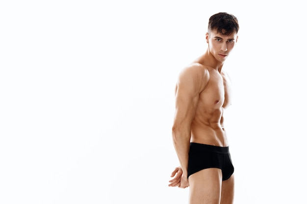 Nude male athlete posing on a light background cropped view of black