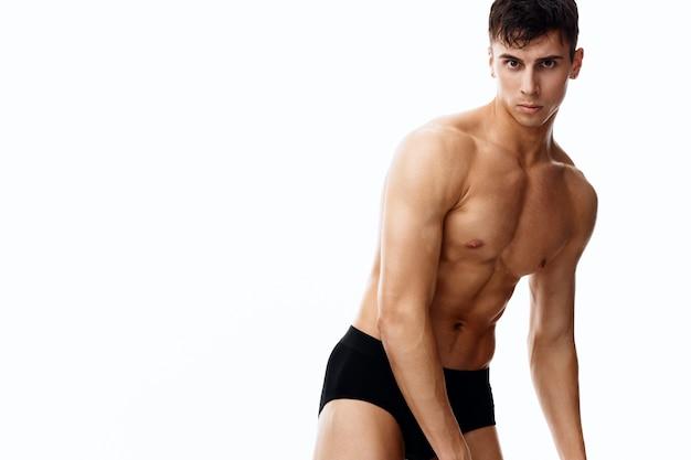 Обнаженный спортсмен-мужчина с надутым торсом, жестикулирующий руками. фото высокого качества