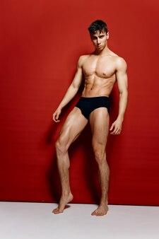 赤い背景と全長の黒いパンティーの裸の男性のボディービルダー
