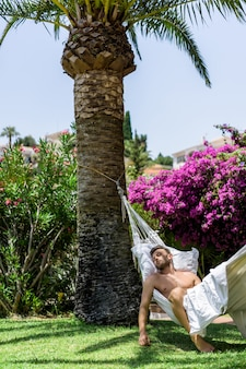 Nude male relaxing in a hammock in the garden.