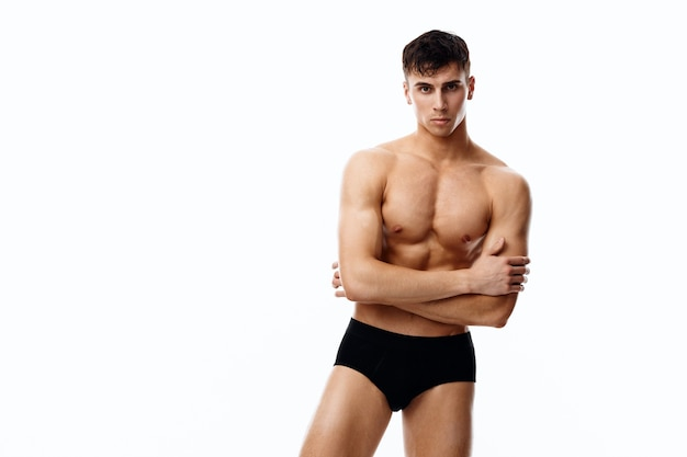 Nude man in black panties holds his hands on his chest