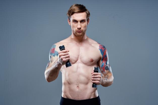 灰色の背景とダンベルの入れ墨のトリミングされたビューでスポーツをしている裸の男