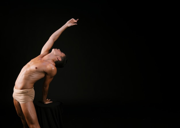 Nude man leaning on chair with hand and pulling up