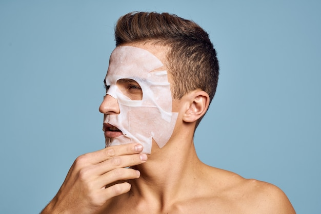 Nude man with white nourishing mask on face on blue space cropped view.