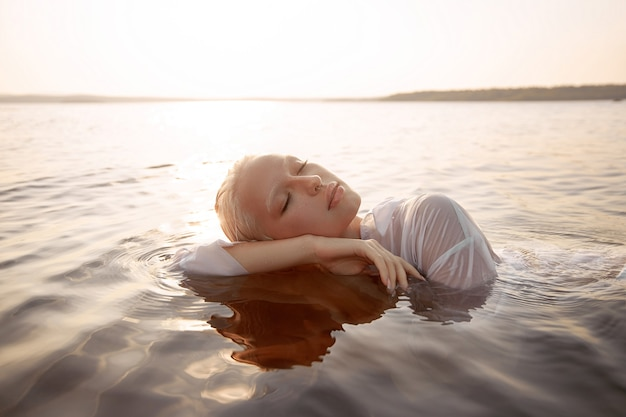 Обнаженная обнаженная сексуальная женщина в воде на закате. красивая блондинка с короткими мокрыми волосами и большой грудью, художественный портрет в море