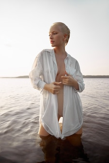 Nude naked sexy woman in water at sunset. beautiful blonde woman with short wet hair and big breasts, art portrait in sea