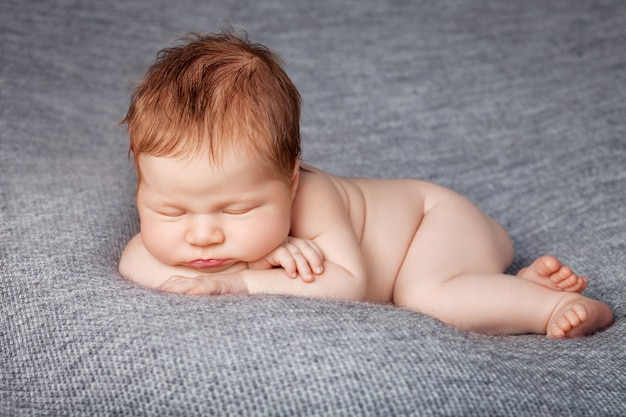 A nude newborn baby curled up and asleep on a gray textured blanket.