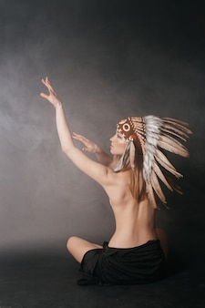Nude perfect woman in the garb of american indians on a gray background