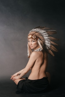 Nude perfect woman in the garb of american indians in the smoke on gray
