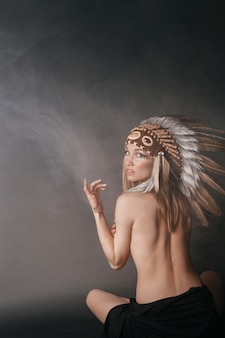 Nude perfect woman in the garb of american indians in the smoke