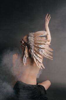 회색 배경의 연기 속에서 아메리칸 인디언 복장을 한 완벽한 누드 여성. 깃털로 만든 모자. 신비로운 신비로운 길, 섹시한 몸매, 아름다운 등