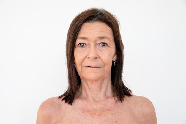 중립적인 표정의 누드 시니어 여성