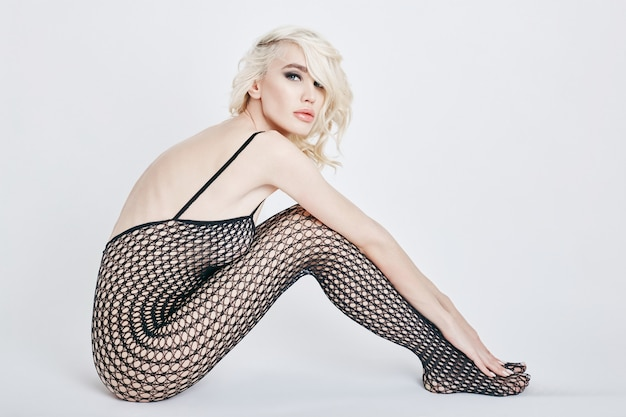 Nude sexy blond woman in lingerie bodysuit with a perfect body sitting on the floor. fetish lingerie into the net on erotic girl. perfect figure women