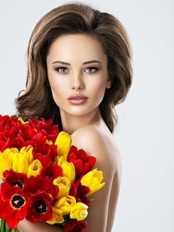 花とヌードセクシーな若い女性。チューリップの花束が魅力的なモデル