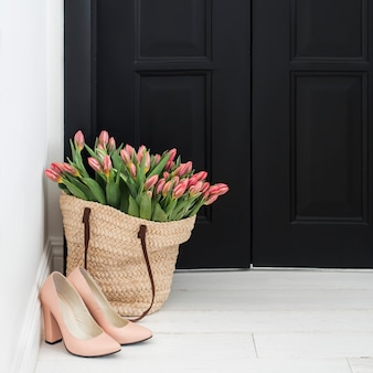 Nude shoes and straw bag with bunch of fresh pink tulips on floor near black door