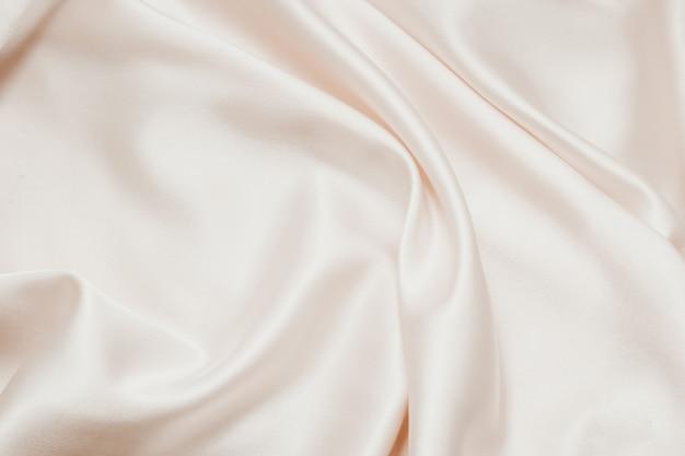 Обнаженная шелковая текстура. атласная нежная пудровая блестящая отделка, красивый фон для дизайнеров