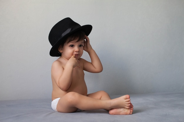 검은 모자를 쓰고 회색 중립 배경에 앉아 그의 입에 손가락을 들고 누드 유아 소년.