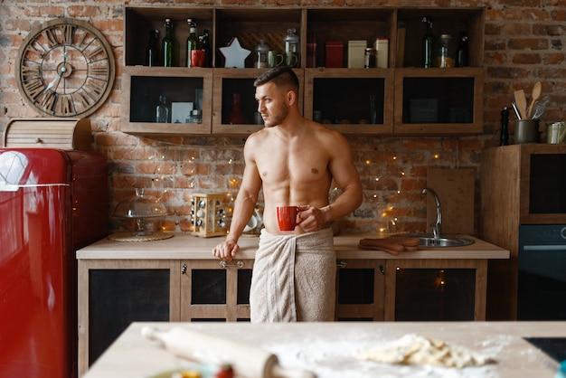 부엌에서 낭만적 인 저녁 식사를 요리하는 누드 수건으로 덮인 남자. 집에서 아침 식사를 준비하는 벌거 벗은 남성 사람, 옷없이 음식 준비